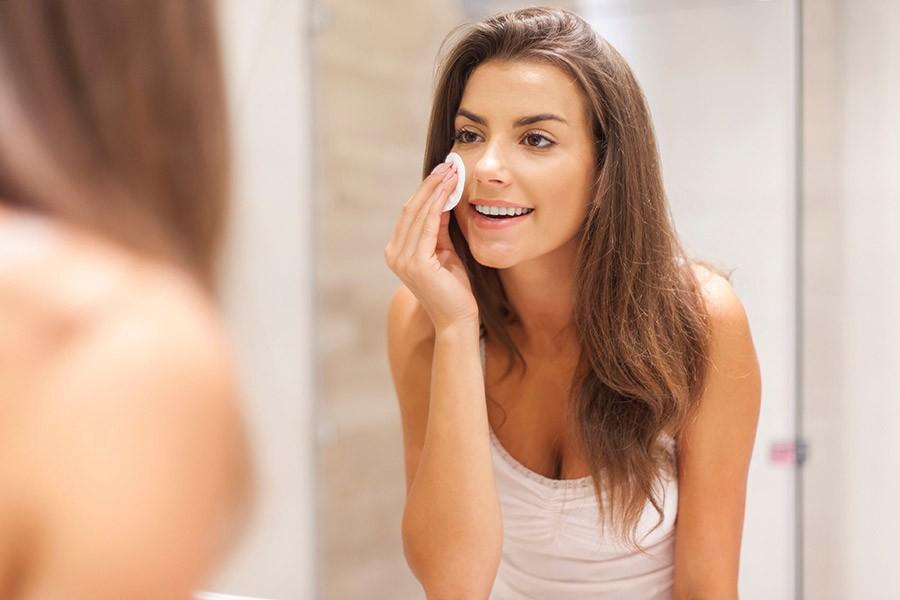 Девушка удаляет макияж с лица с помощью средства для демакияжа